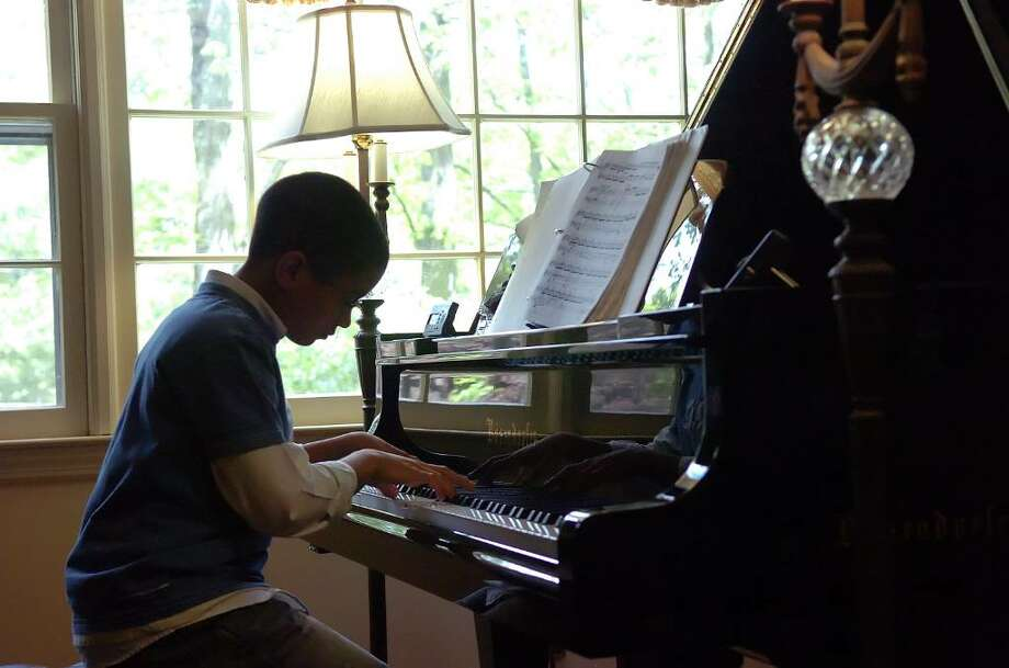 Seth Blumer, 11, plays on a grand piano in the quiet of his Stamford home Sunday May 16, 2010.  Blumer is performing a benefit recital at Northeast Elementary School Friday May 21 with all proceeds going toward the school's music program. The program will include Liszt, Bach, Beethoven and Ravel. Photo: Keelin Daly / Stamford Advocate