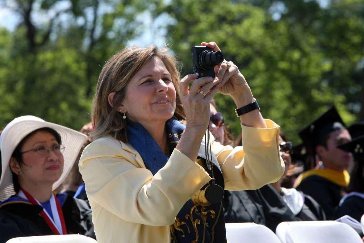 Susan St James takes a picture of her husband, Dick Ebersol, as he receives an honorary degree at Sacred Heart University's Commencement ceremony on Sunday.