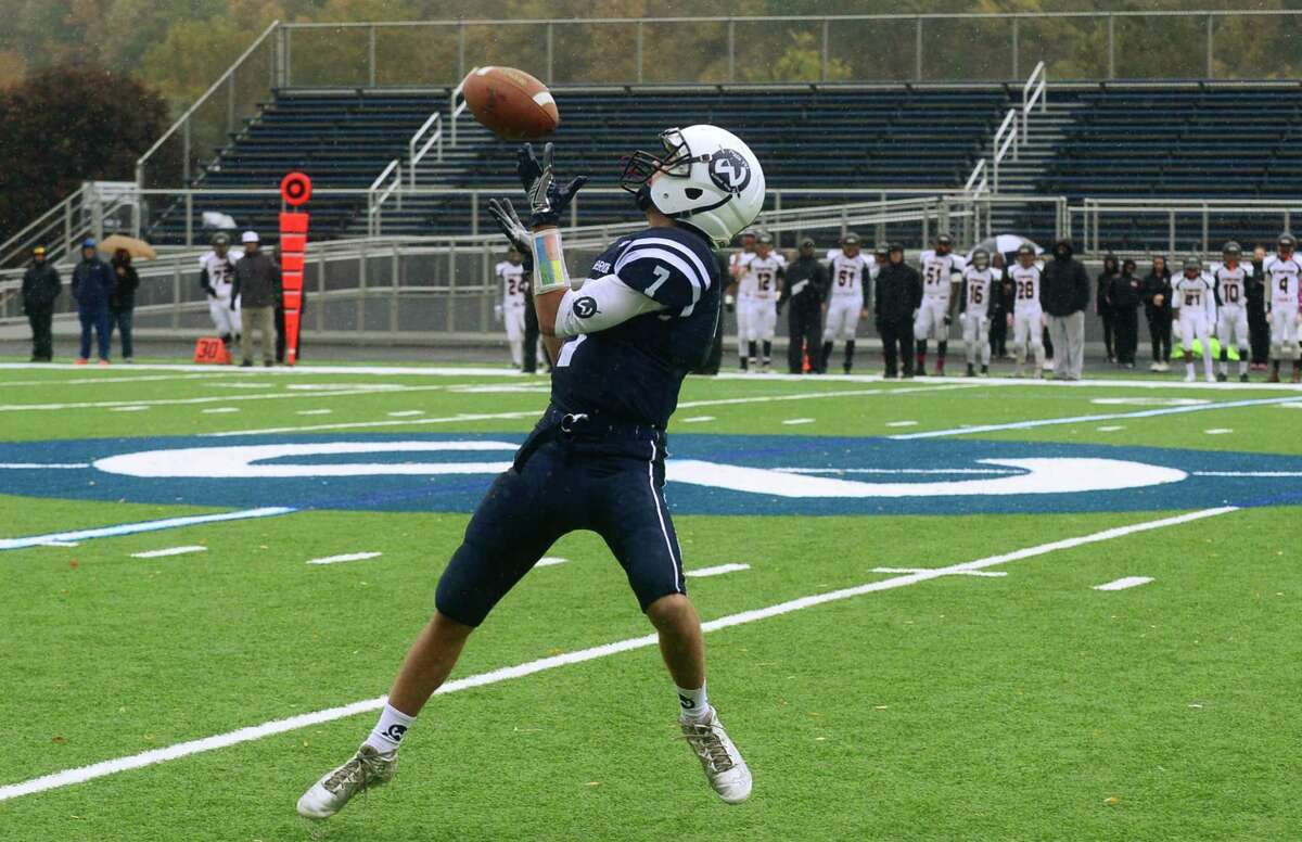 Wilton High School football player Joseph Pozzi receives a pass on a trick play during their first possession against Stamford during their FCIAC game at Fujitani Field in Wilton on Saturday.