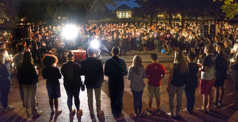 University of Illinois students attend a candlelight vigil in remembrance of Sunday's shootings and death of George Korchev of Mundelein at the school campus in Urbana, Ill., Tuesday, Sept. 27, 2016. (Robin Scholz/The News-Gazette via AP)