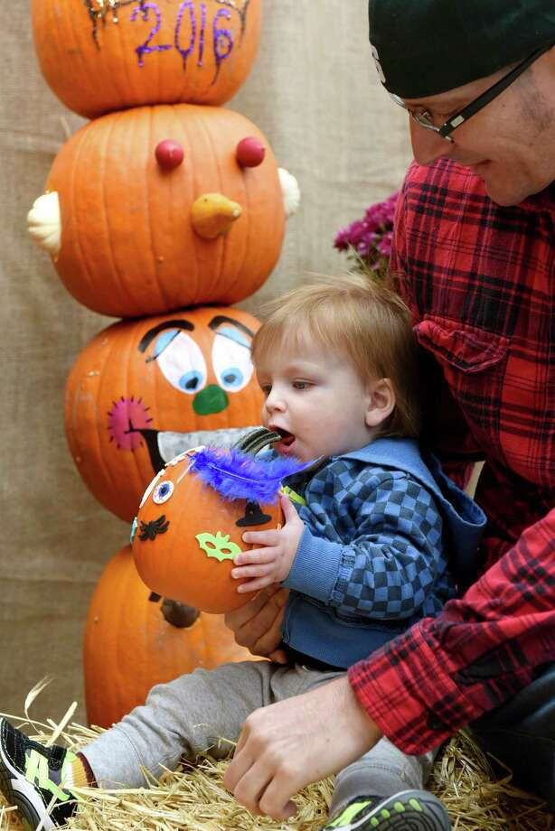 Zayden Zuloaga, 1, of Guilderland gives his pumpkin a bite test during the on 7th Annual Gade Farm PumpkinFest on Saturday, Oct. 22, 2016, at Gade Farm in Guilderland, N.Y. Joining Zayden is his father, Damian Zuloaga. (Cindy Schultz / Times Union) Photo: Cindy Schultz / Albany Times Union