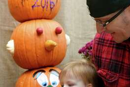 Zayden Zuloaga, 1, of Guilderland gives his pumpkin a bite test during the on 7th Annual Gade Farm PumpkinFest on Saturday, Oct. 22, 2016, at Gade Farm in Guilderland, N.Y. Joining Zayden is his father, Damian Zuloaga. (Cindy Schultz / Times Union)