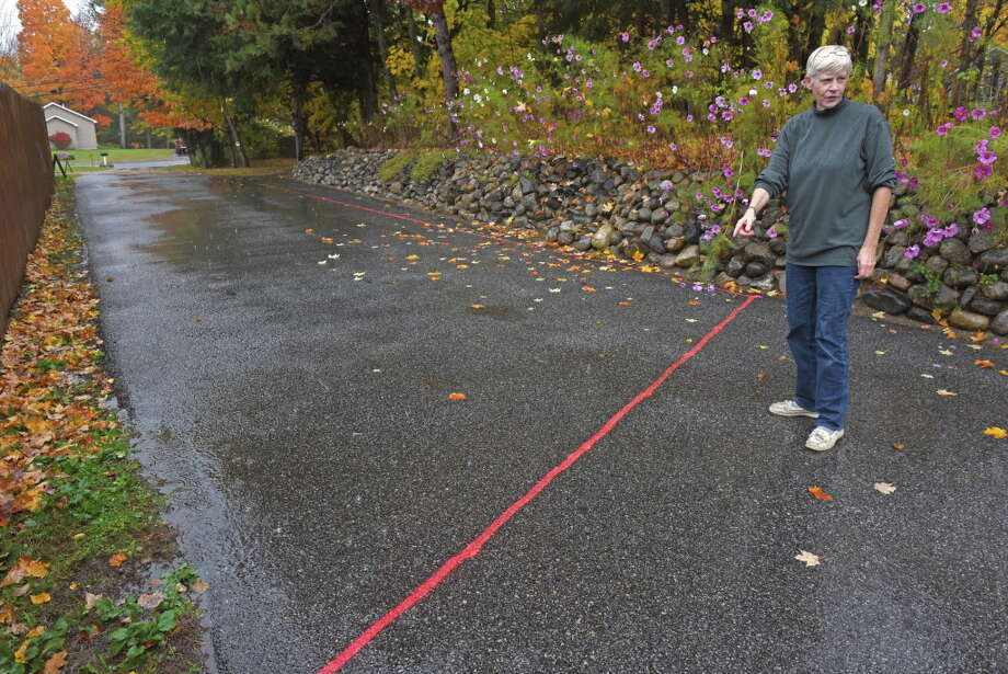 Catherine LaFond-Evans shows the lines her neighbor had drawn on her driveway where he intends to build a fence on Thursday Oct. 20, 2016 in Warrensburg , N.Y. The Brooklyn owner of the house next door is seeking to build a fence across her driveway, arguing the easement her parents gave her is in the wrong place. Its' because she complained about the noisy tenants who rent his house. (Michael P. Farrell/Times Union) Photo: Michael P. Farrell / 20038453A