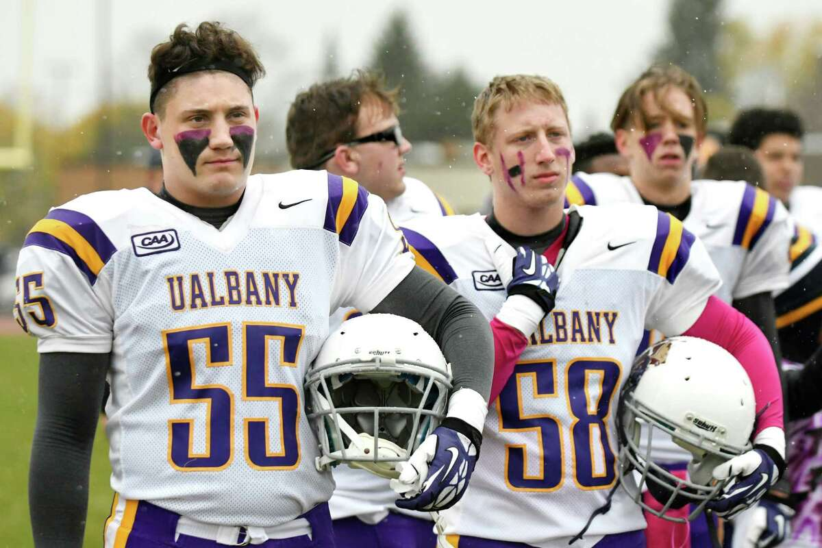 Holy Trinity's David Quell, left, and his teammates wear borrowed UAlbany jerseys for their Class C quarterfinal football game against Hoosic Valley on Saturday, Oct. 22, 2016, at Hoosic Valley High in Schaghticoke, N.Y. The team lost their football equipment in fire. (Cindy Schultz / Times Union)