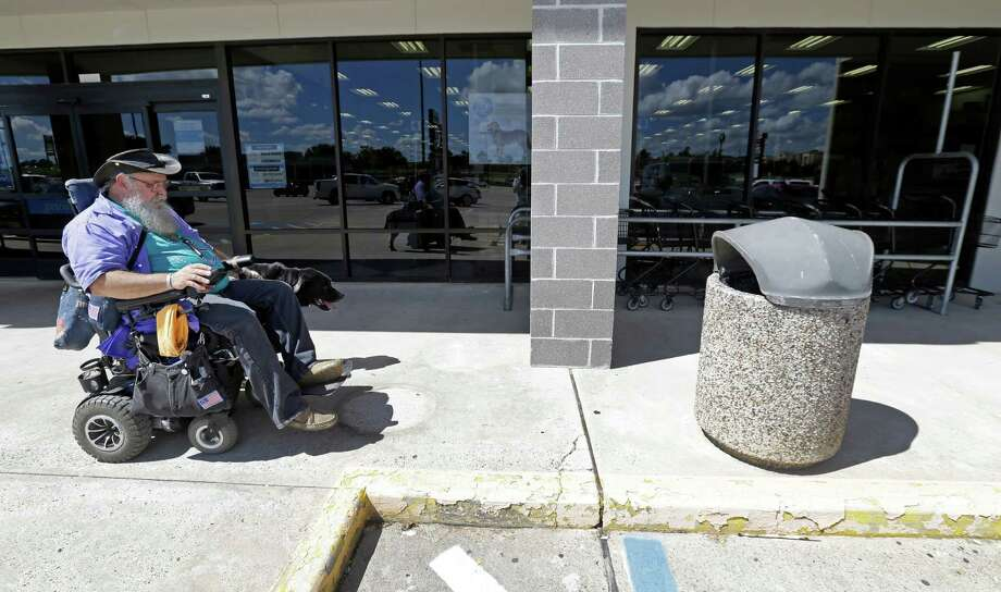James Van Winkle with his service dog, Roku, encounters a trashcan on a shopping center sidewalk that blocked the access for his wheelchair on Sept. 14, in Conroe. A department manager at the nearby store said the trashcan was placed in the spot to cover a hole in the sidewalk. Photo: Melissa Phillip, Staff / © 2016 Houston Chronicle