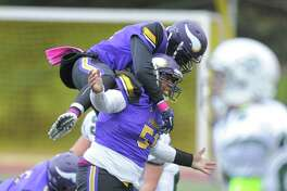 Westhill's Alan Kowlin leaps onto the back of Quran Cameron in celebration following Cameron's hit on Norwalk QB Krishtjan Frrokaj. The play lead to a game-ending fumble on Saturday in Stamford.