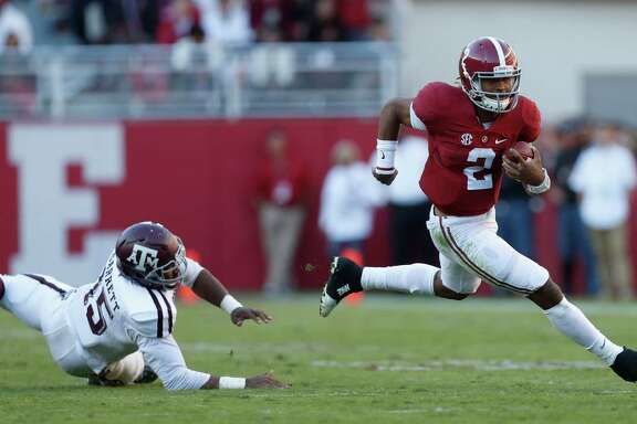 Alabama Crimson Tide quarterback Jalen Hurts (2) runs the ball as Texas A&M Aggies defensive lineman Myles Garrett (15) tried to stop him during the third quarter of a college football game at Bryant-Denny Stadium, Saturday,Oct. 22, 2016 in Tuscaloosa.
