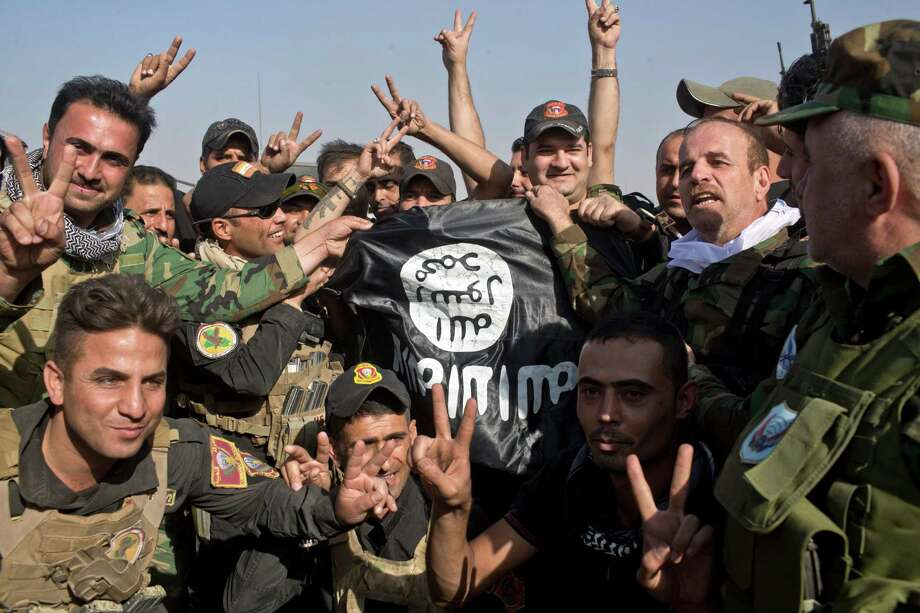 Iraqi and Kurdish forces hold an Islamic State flag found in in the town of Bartella, Iraq, Saturday, Oct. 22, 2016. Iraqi forces retook Bartella, around 15 kilometers east of Mosul, earlier this week, but are still facing pockets of resistance in the area. (AP Photo/Marko Drobnjakovic) ORG XMIT: XMD105 Photo: Marko Drobnjakovic / Copyright 2016 The Associated Press. All rights reserved.
