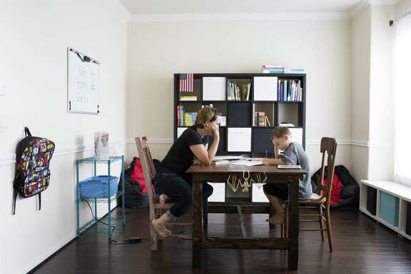Heidi Walker sits across from her son Roanin Walker, 7, while he studies at his home classroom in Kingwood, Thursday, Aug. 25, 2016. Heidi and her husband decided to homeschool Roanin this academic year after he was denied special education. Roanin has been diagnosed with attention deficit disorder, anxiety and sensory processing disorder. ( Marie D. De Jesus / Houston Chronicle )
