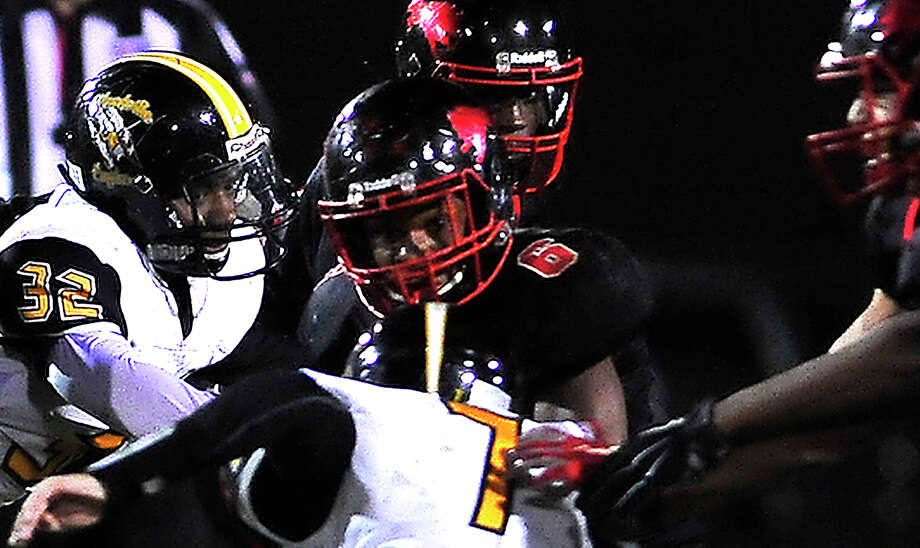 Kountze's Keyshawn Adams runs up against a duo of Woodville's defenders as he carries the ball during Friday's game at Kountze. Photo taken Friday, October 21, 2016 Kim Brent/The Enterprise Photo: Kim Brent / Beaumont Enterprise
