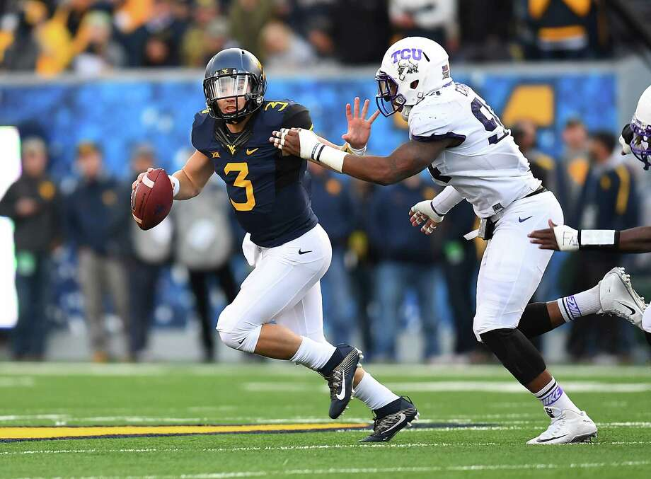 West Virginia quarterback Skyler Howard (3) eludes TCU defender Josh Carraway in the second quarter of Saturday's game at Morgantown, W.Va. Photo: Joe Sargent, Stringer / 2016 Getty Images