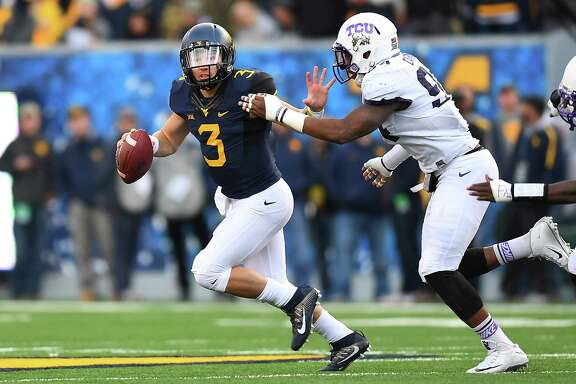 West Virginia quarterback Skyler Howard (3) eludes TCU defender Josh Carraway in the second quarter of Saturday's game at Morgantown, W.Va.