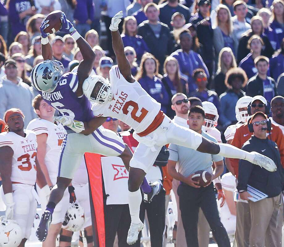 Texas cornerback Kris Boyd, right, uses his head in a failed attempt to dislodge the ball from the hands of Kansas State wide receiver Deante Burton in the first quarter Saturday at Bill Snyder Family Stadium in Manhattan, Kan. Photo: Bo Rader, MBR / Wichita Eagle