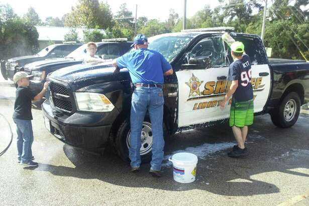 Volunteers with Faith Tabernacle Church in Tarkington wash sheriff's vehicles during a law enforcement appreciation event on Oct. 15.