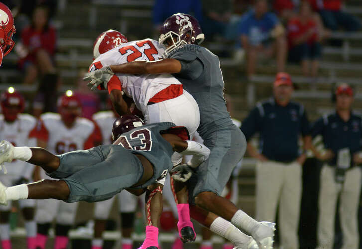 Kempner senior safety Resean Foster, left, and junior linebacker Jacob Mangum-Farrar, right, wrap up Dulles senior running back Frank Marquise (22) on a 2nd quarter running play in their District 20-6A matchup at Mercer Stadium on Saturday, Oct. 22, 2016. (Photo by Jerry Baker/Freelance)