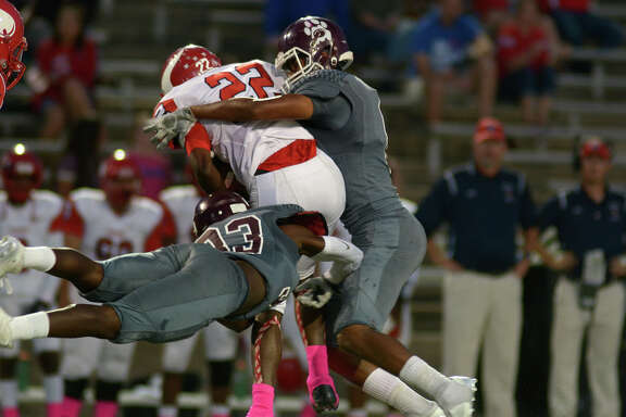 Kempner safety Resean Foster, left, and linebacker Jacob Mangum-Farrar wrap up Dulles running back Frank Marquise in the second quarter of Saturday night's District 20-6A game at Mercer Stadium. Kempner won 49-21.