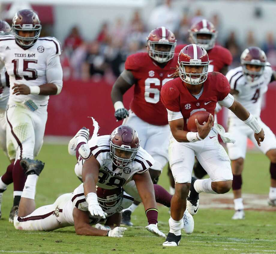 Alabama Crimson Tide quarterback Jalen Hurts (2) on his 27-yard run for a touchdown as Texas A&M Aggies linebacker Shaan Washington (33) and  Kingsley Keke (88) tried to bring him down during the fourth quarter of a college football game at Bryant-Denny Stadium, Saturday,Oct. 22, 2016 in Tuscaloosa.   ( Karen Warren / Houston Chronicle ) Photo: Karen Warren, Staff Photographer / 2016 Houston Chronicle