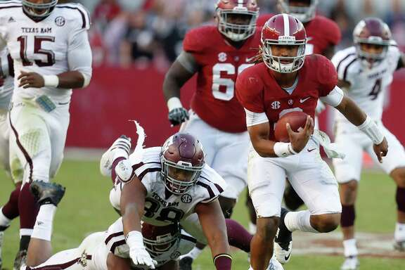 Alabama Crimson Tide quarterback Jalen Hurts (2) on his 27-yard run for a touchdown as Texas A&M Aggies linebacker Shaan Washington (33) and  Kingsley Keke (88) tried to bring him down during the fourth quarter of a college football game at Bryant-Denny Stadium, Saturday,Oct. 22, 2016 in Tuscaloosa.   ( Karen Warren / Houston Chronicle )