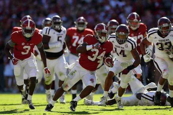 Alabama's Damien Harris (34) rushes past A&M's Justin Evans (14) during his team's victory on Saturday. Harris finished with 17 rushes for 128 yards.