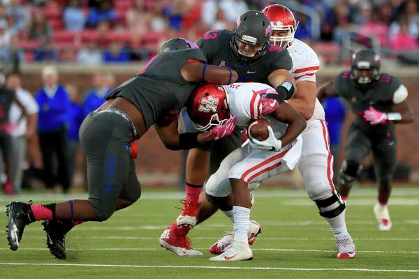 UH quarterback Greg Ward Jr., center, is sacked by SMU's Demerick Gary, left, and Mason Gentry in the first half.