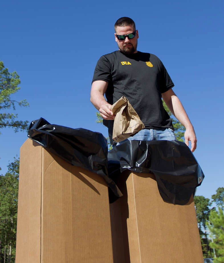 Gerrit Wolfhagen, a task force officer with the Conroe Police Department, drops a bag of medication into a bin for later disposal during the DEA's annual pill take back day at the Conroe Police Department and Municipal Courts building Saturday, Oct. 22, 2016, in Conroe. Photo: Jason Fochtman, Staff Photographer / Houston Chronicle