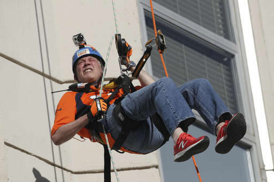 Colorado Gov. John Hickenlooper rappels down a downtown high-rise building as part of the Over The Edge fundraiser which benefits the Cancer League of Colorado, late Thursday, Sept. 8, 2016, in Denver. (AP Photo/David Zalubowski)
