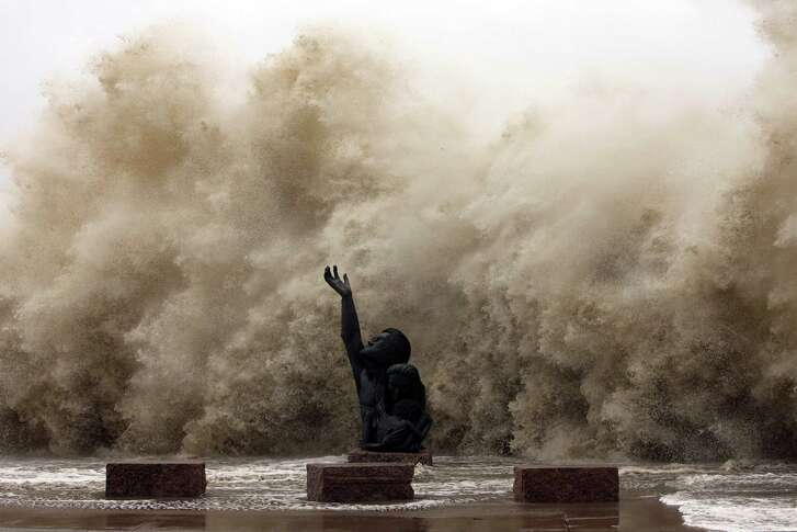 Waves crash into the seawall reaching over the memorial to the hurricane of 1900 as Hurricane Ike hit Galveston, later damaging 75 percent of structures on the island.