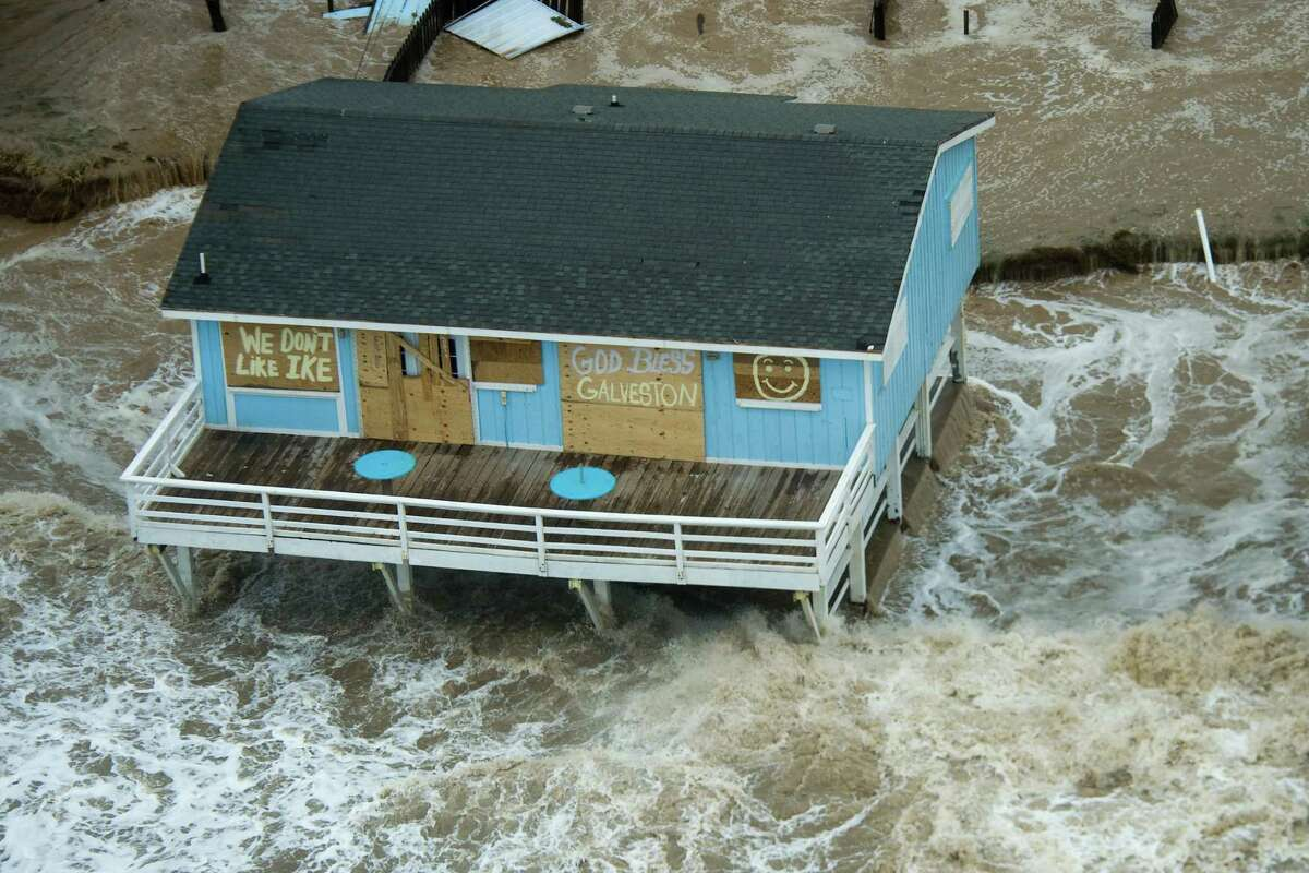 """Surf surrounds a beach house with the messages """"We Don't Like Ike,"""" and """"God Bless Galveston"""" painted on plywood covering the windows of the house on Galveston Island as Hurricane Ike approaches the Texas Gulf Coast, Friday, Sept. 12, 2008. ( Smiley N. Pool / Chronicle )"""
