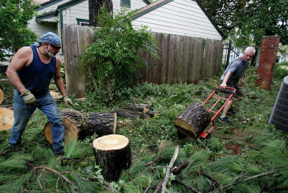 Alex Martinez, left, helps his Garden Oaks neighbor Jerry Kennedy chop up a tree trunk that fell on Kennedy's house in the aftermath of Hurricane Ike, which hit the region in 2008.