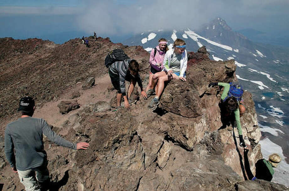 In this 2012 photo, from left, Shawn Foster, Carson Pemble, Emily Read, Brittany Pemble and Megan Pemble explore the summit of South Sister, west of Bend, Ore. Officials with the Deschutes National Forest and the Willamette National Forest are considering changes to possibly limit use in the most popular areas of the Three Sisters Wilderness are in order to maintain the wilderness character of those locations. (Joe Kline /The Bulletin via AP)