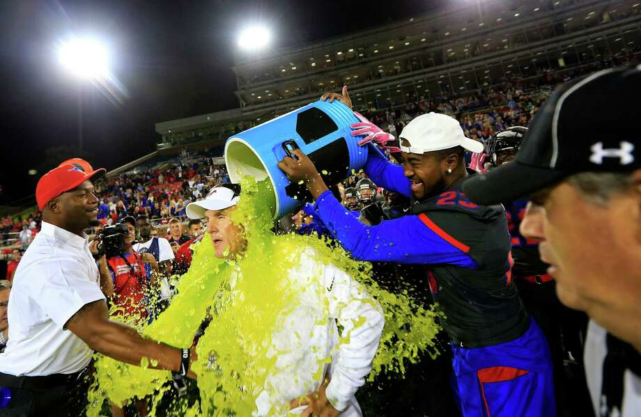 SMU coach Chad Morris is doused by defensive end Nick Horton (23) late in the fourth quarter against Houston in an NCAA college football game, Saturday, Oct. 22, 2016, in Dallas. SMU won 38-16. (AP Photo/Ron Jenkins) Photo: Ron Jenkins, Associated Press / FR171331 AP