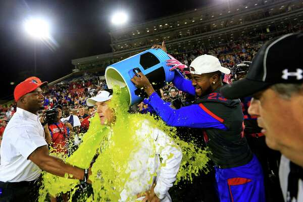 SMU coach Chad Morris is doused by defensive end Nick Horton (23) late in the fourth quarter against Houston in an NCAA college football game, Saturday, Oct. 22, 2016, in Dallas. SMU won 38-16. (AP Photo/Ron Jenkins)
