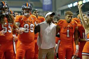 UTSA Roadrunners head coach Frank Wilson (center) stands with players Josiah Tauaefa (55), from left,  Baylen Baker (99), Devron Davis (1) and others during the school song after the game with UTEP Saturday Oct. 22, 2016 at the Alamodome. UTEP won in five overtimes 52-49.