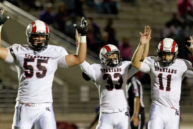 Porter quarterback Jacob Hall (11), offensive linemen Caleb Johnson (55) and running back Cory Cowan (33) raise their hands in celebration after Hall's 19-yard touchdown pass to wide receiver Sevonne Rhea during the fourth quarter of a District 21-5A high school football game at Turner Stadium Saturday, Oct. 22, 2016, in Humble.