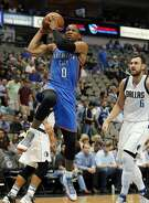 Oklahoma City Thunder guard Russell Westbrook (0) controls the ball past Dallas Mavericks' Andrew Bogut (6) of Australia on a drive to the basket in the first half of a preseason NBA basketball game, Tuesday, Oct. 11, 2016, in Dallas. (AP Photo/Tony Gutierrez)