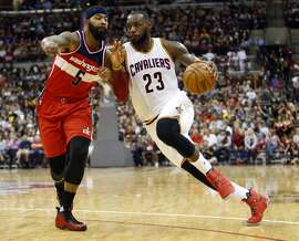 Cleveland Cavaliers' LeBron James, right, drives to the basket against Washington Wizards' Markieff Morris during the first half of an NBA preseason basketball game, Tuesday, Oct. 18, 2016, in Columbus, Ohio. The Wizards defeated the Cavaliers 96-91. (AP Photo/Jay LaPrete)
