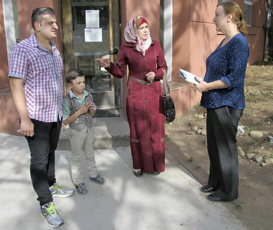 In this Friday, Sept. 2, 2016 photo, Syrian refugees Abdullah, left, Fatema, second from right, and their son Ayham, speak with Liese Klein, right, development and communications manager for Integrated Refugee & Immigrant Services outside the agency's office in New Haven, Conn. The family was diverted to Connecticut last year after Indiana Gov. Mike Pence said they were not welcome in that state. In their new home state, they have been received warmly by many, including Connecticut's Democratic governor, but they say they also have faced difficulties with finding work and with discrimination. (AP Photo/Pat Eaton-Robb)