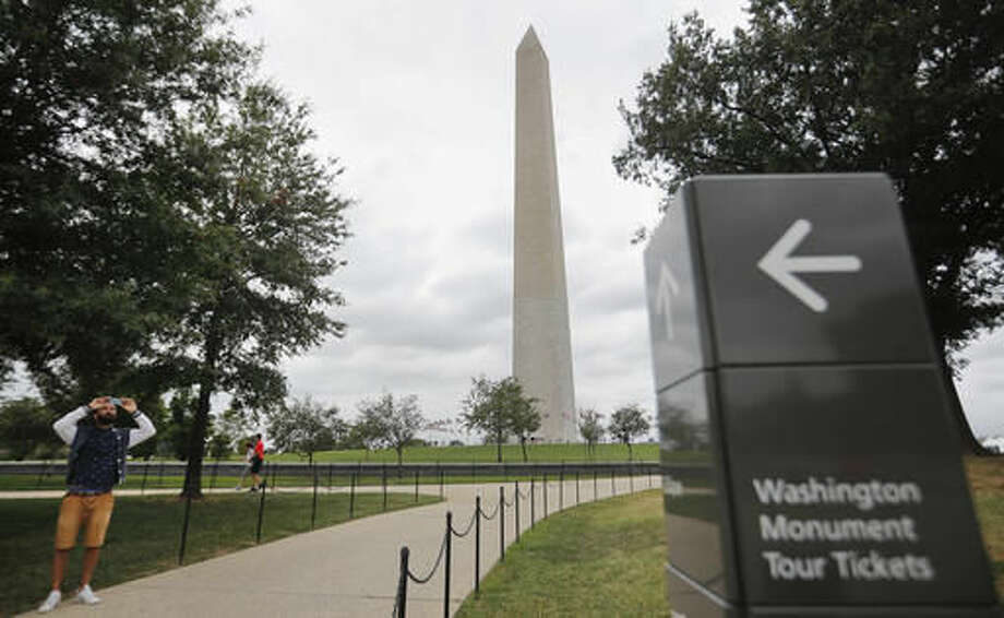 A tourist stop to take a picture near the Washington Monument on the National Mall in Washington, Monday, Sept. 26, 2016. Elevator trouble closes Washington Monument indefinitely the National Park Service says the Washington Monument will be closed indefinitely because of ongoing problems with its elevator. The park service said in a statement Monday that the monument will remain closed until its elevator control system can be modernized. The lone elevator that takes visitors to the top of the 555-foot obelisk has broken down frequently over the past two years. (AP Photo/Pablo Martinez Monsivais)
