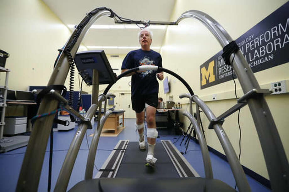 In this Friday, Aug. 12, 2016 photo, David Moran runs on a treadmill with sensors attached to his legs and feet in Ann Arbor, Mich. A University of Michigan lab, The Michigan Performance Research Laboratory, which is part of the School of Kinesiology, is offering runners an in-depth assessment designed to help them improve their form. The consultations last around two hours and include footwear, musculoskeletal and postural evaluations by a physical therapist as well as footprint pressure and full-body 3-D gait analyses. (AP Photo/Paul Sancya)