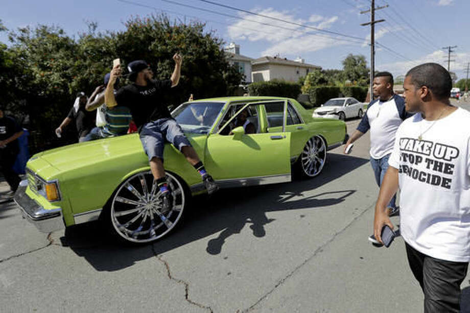 """People ride on the hood of a car during a protest, Wednesday, Sept. 28, 2016, in El Cajon, Calif. Dozens of demonstrators on Wednesday protested the killing of a black man shot by an officer after authorities said the man pulled an object from a pocket, pointed it and assumed a """"shooting stance."""" (AP Photo/Gregory Bull)"""