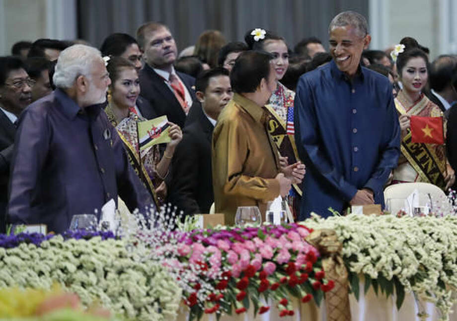 From left, Indian Prime Minister Narendra Modi, Brunei's Sultan Hassanal Bolkiah and U.S. President Barack Obama, stand at their seats as they arrive at the ASEAN Gala Dinner at the National Convention Center in Vientiane, Laos, Wednesday, Sept. 7, 2016. (AP Photo/Carolyn Kaster)