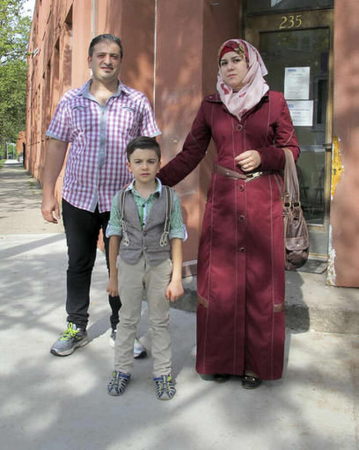 In this Friday, Sept. 2, 2016 photo, Syrian refugees Abdullah, left, Fatema, right, and their son Ayham, 5, pose for a photo outside the Refugee & Immigrant Services office in New Haven, Conn. The family was diverted to Connecticut last year after Indiana Gov. Mike Pence said they were not welcome in that state. In their new home state, they have been received warmly by many, including Connecticut's Democratic governor, but they say they also have faced difficulties with finding work and with discrimination. (AP Photo/Pat Eaton-Robb)