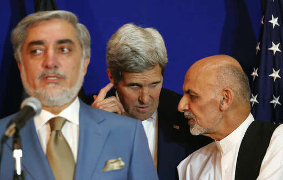 FILE - In this Friday, Aug. 8, 2014 file photo, Afghan presidential candidate Abdullah Abdullah, from left, speaks, while another candidate Ashraf Ghani Ahmadzai talks to U.S. Secretary of State John Kerry during a joint press conference in Kabul, Afghanistan. Afghanistan's unity government is expected to remain in place despite the formal expiration on Wednesday, Sept. 28, 2016 of the U.S.-brokered deal between two electoral rivals whose internal feuding has undermined efforts to battle the Taliban and stabilize the country. (AP Photo/Rahmat Gul File)