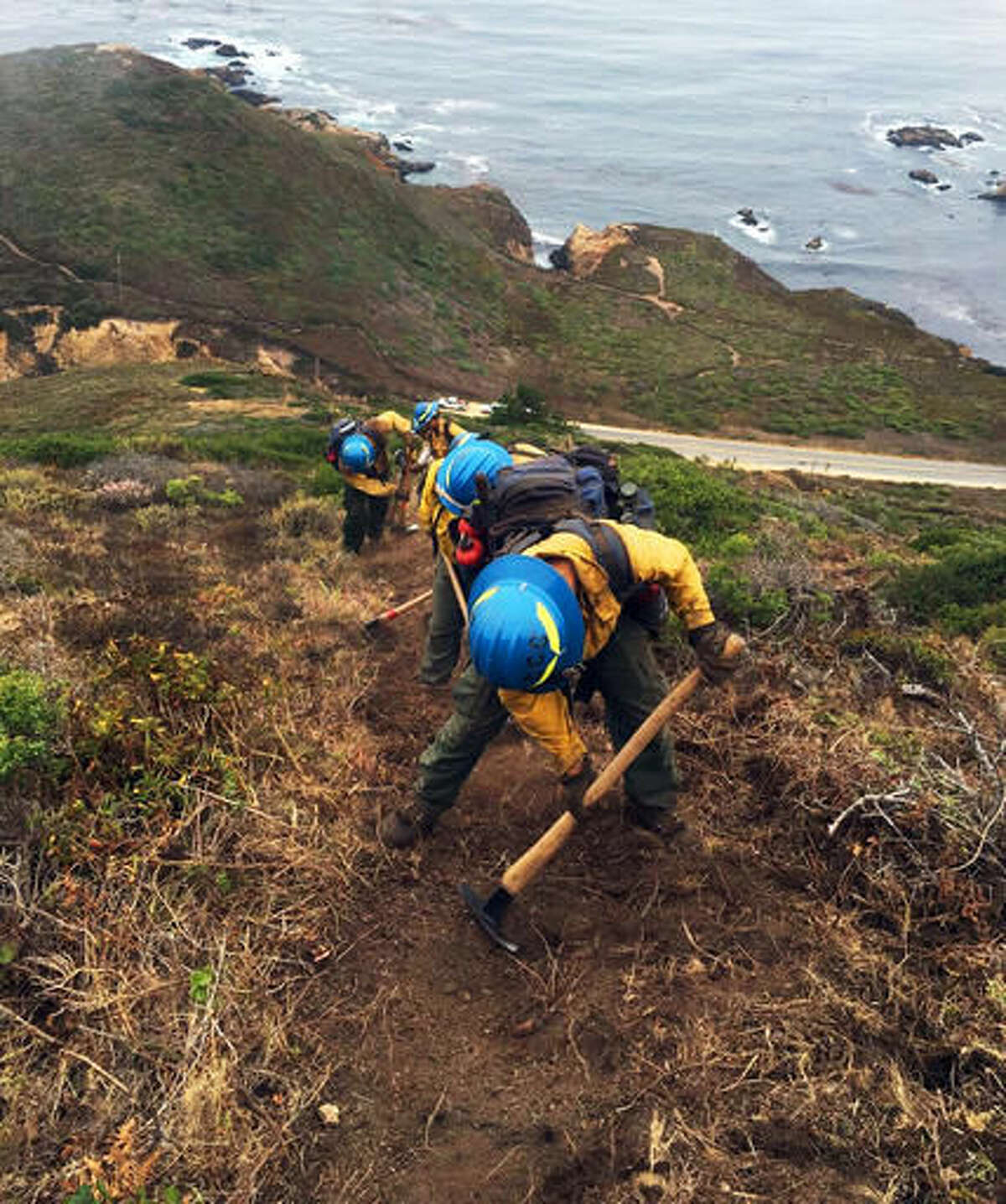 In this Aug. 1, 2016 photo provided by the California Conservation Corps, a civilian firefighter crew cuts fire lines as they work the Soberanes Fire in Garrapata State Park near Big Sur, Calif. California officials faced with a shrinking pool of inmate firefighters during major blazes are increasingly turning to the California Conservation Corps. The program reopened a camp this year to train multiple crews of young civilian firefighters to do the same backbreaking work as inmates. (Andrae Aldrete/California Conservation Corps via AP)