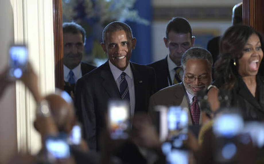 President Barack Obama walks into the Grand Foyer with Lonnie Bunch, Director of the Smithsonian Museum of African American History and Culture, and first lady Michelle Obama, to speak at a reception for the museum opening at the White House in Washington, Friday, Sept. 23, 2016. (AP Photo/Susan Walsh)