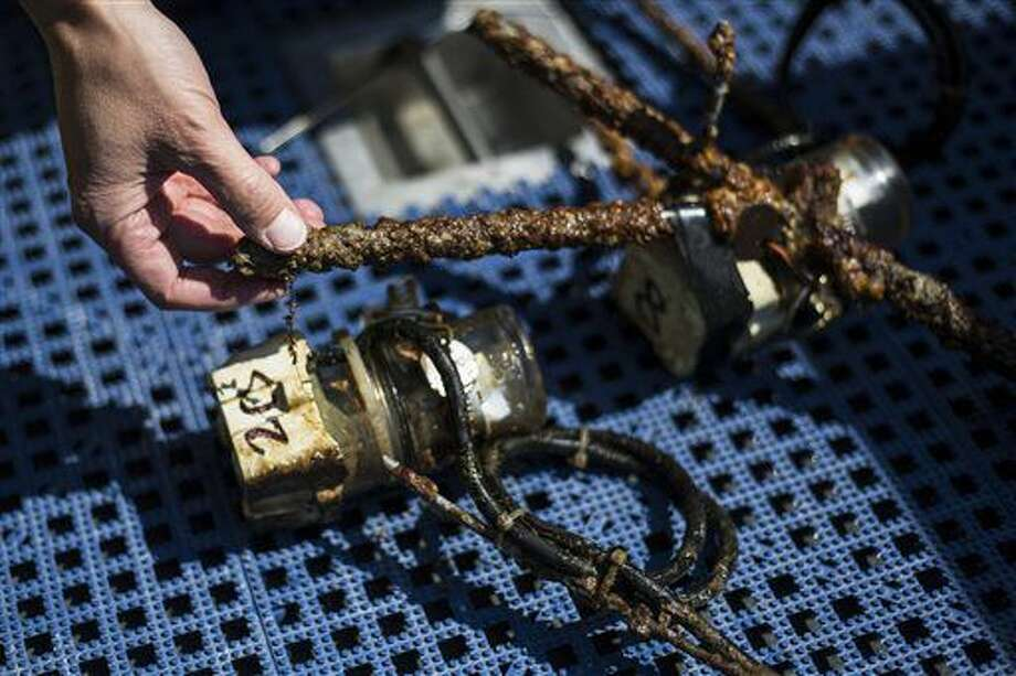 In this Aug. 24, 2016 photo, Global Foundation for Ocean Exploration Vice President Melissa Ryan touches decades of buildup on temperature gauges that the foundation's new aquatic robot Yogi retrieved from the lake's bottom on Yellowstone Lake, in Yellowstone National Park, Wyo. (Ryan Dorgan/Jackson Hole News & Guide via AP)