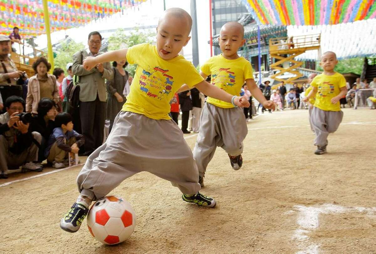SEOUL, SOUTH KOREA - MAY 15: Young four and five-year-old children play a friendly game of soccer underneath colorful hanging paper lanterns at the Chogye Temple on May 15, 2010 in Seoul, South Korea. The game is known as the Little Monk Soccer Match and is part of the celebration surrounding '21 Days of Little Monk' which honors Buddha's birthday as well as the upcoming FIFA 2010 World Cup. (Photo by Chung Sung-Jun/Getty Images)