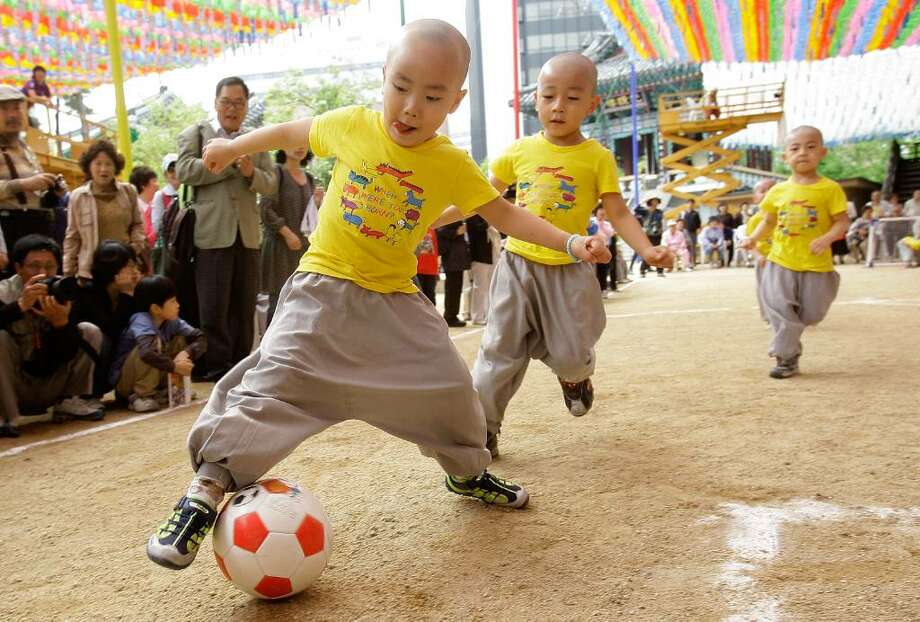 SEOUL, SOUTH KOREA - MAY 15:  Young four and five-year-old children play a friendly game of soccer underneath colorful hanging paper lanterns at the Chogye Temple on May 15, 2010 in Seoul, South Korea. The game is known as the Little Monk Soccer Match and is part of the celebration surrounding '21 Days of Little Monk' which honors Buddha's birthday as well as the upcoming FIFA 2010 World Cup.  (Photo by Chung Sung-Jun/Getty Images) Photo: Chung Sung-Jun, Getty Images / 2010 Getty Images