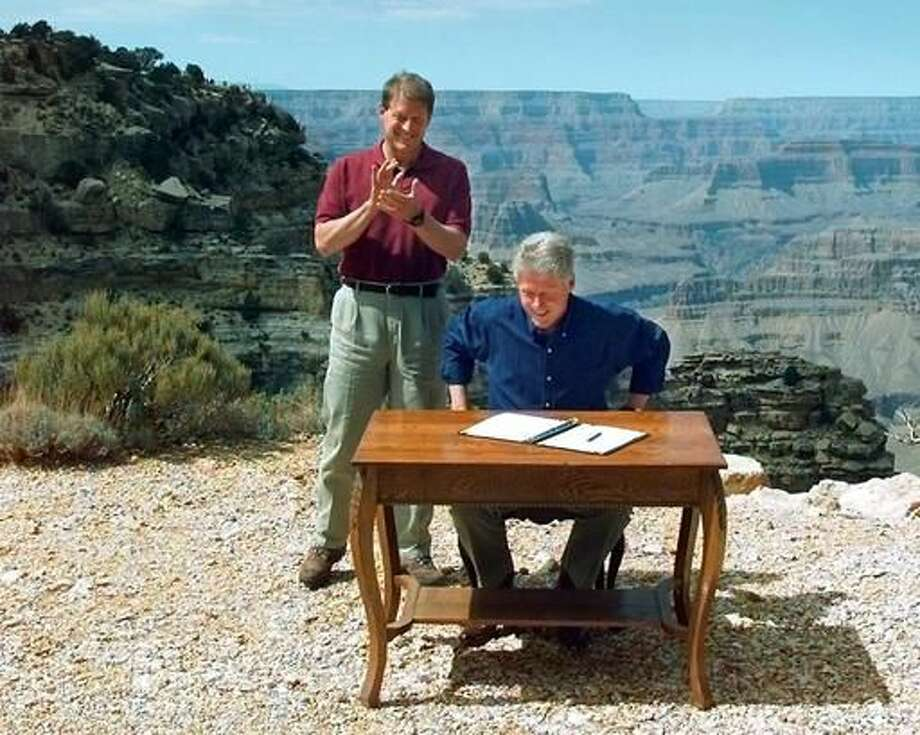 FILE - In this Sept. 18, 1996, file photo, Vice President Al Gore applauds after President Bill Clinton signs a bill designating about 1.7 million acres of land in southern Utah's red-rock cliff as the Grand Staircase-Escalante National Monument, at the Grand Canyon National Park, in Arizona. As Utah waits to see if President Barack Obama will designate a new national monument in the state, the 20th anniversary of the Grand Staircase Escalante-National Monument rekindled memories of an event that ignited simmering western frustrations about federal ownership of public land. (AP Photo/Doug Mills, File)