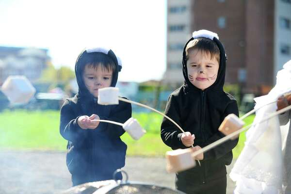 Three-year-old twins Preston, right, and Henry Updike toast marshmallows during the Mill River Park Spooktacular in Stamford, Conn. on Sunday, Oct. 23, 2016.